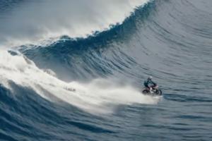 Surfista corre olas gigantes en una motocicleta